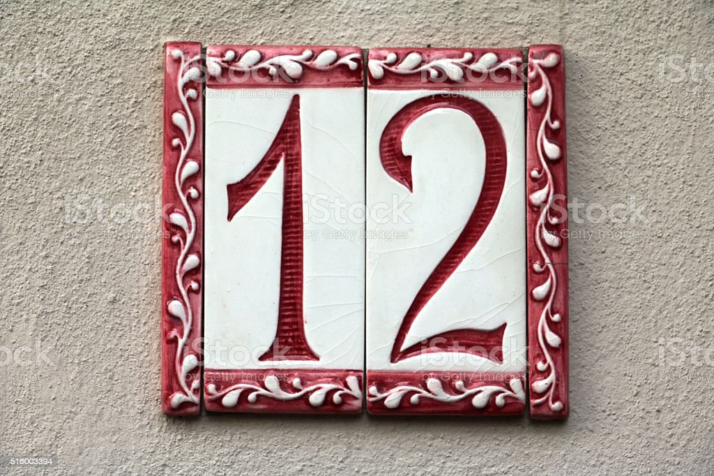 house number twelve at a beige wall stock photo