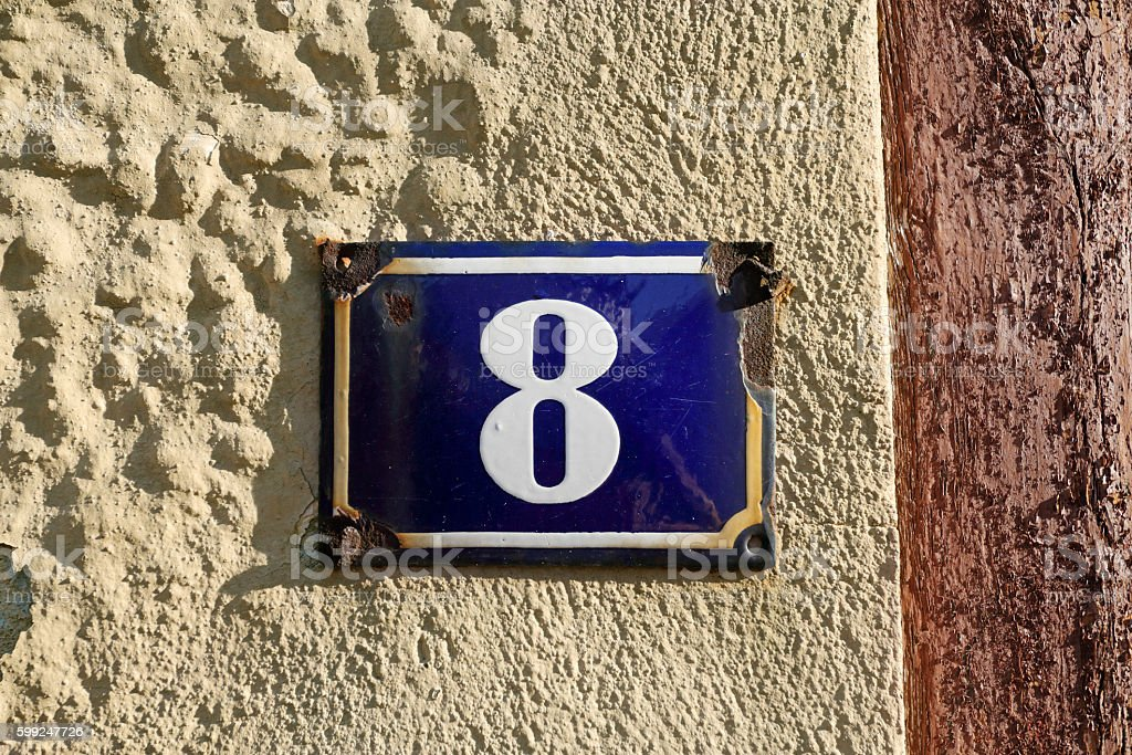House number: White 8 on old-fashioned blue enamel sign stock photo