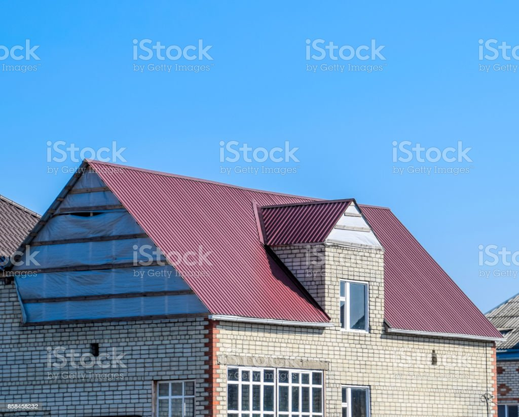 House of cinder block. House with plastic windows and roof of corrugated sheet. Roofing of metal profile wavy shape on the house with plastic windows stock photo