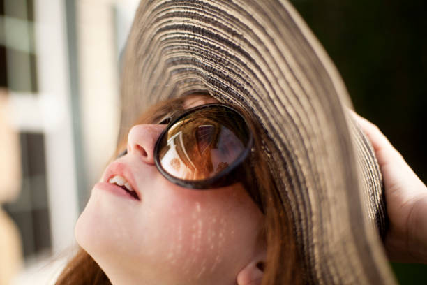 House of her dreams Girl in the sunglasses, yellow dress and big hat looking to house. Focus on the house's reflection in the sunglasses. dark spots face stock pictures, royalty-free photos & images