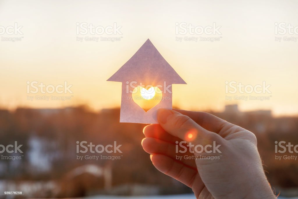 House of paper with a heart in the hand . House of paper with a heart in the hand on the rising sun background. Backgrounds Stock Photo