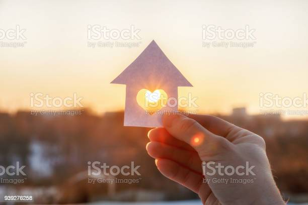 Photo of House of paper with a heart in the hand .