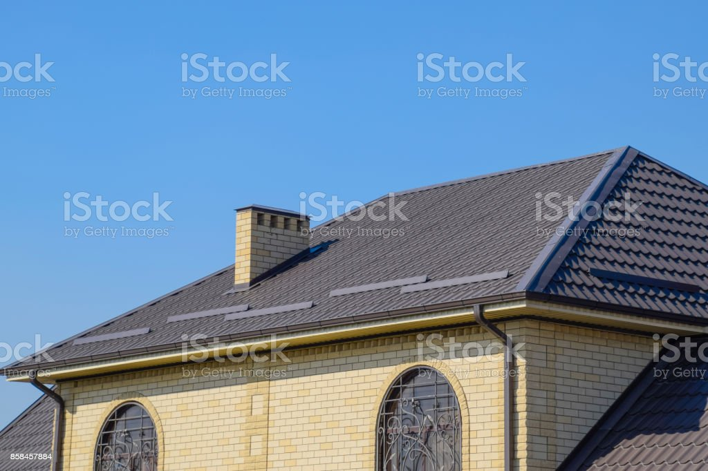 House of yellow brick and brown corrugated roof made of metal. Lattices on the windows. stock photo