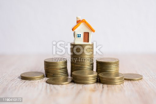 House on a pile of coins Unsorted. Business Startup. mortgage and real estate investment. Is about to start saving money for an investment home purchase.
