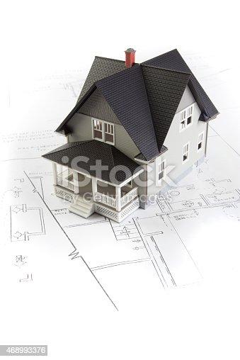 Toy house on blueprints isolated