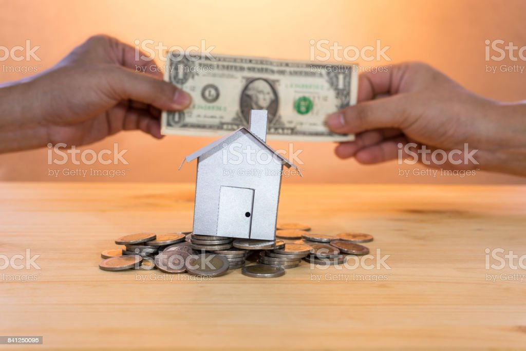 house on coin heap with hand pay dollar on background. money saving concept to buy home stock photo