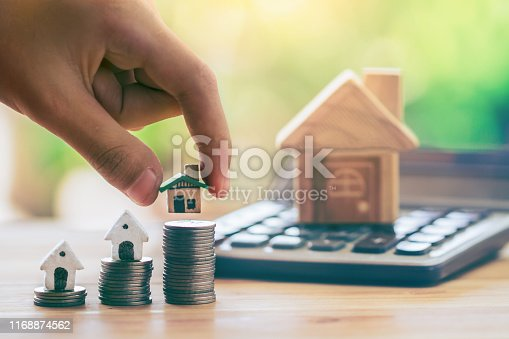 istock House on coins and house put on calculator. Man's hand putting home. planning savings money of coins to buy a home concept for property ladder, 1168874562