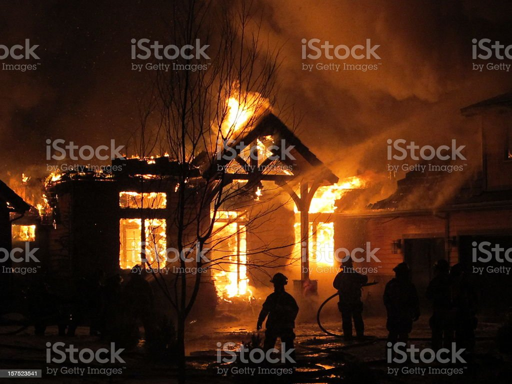 House on fire that the firemen are trying to extinguish stock photo