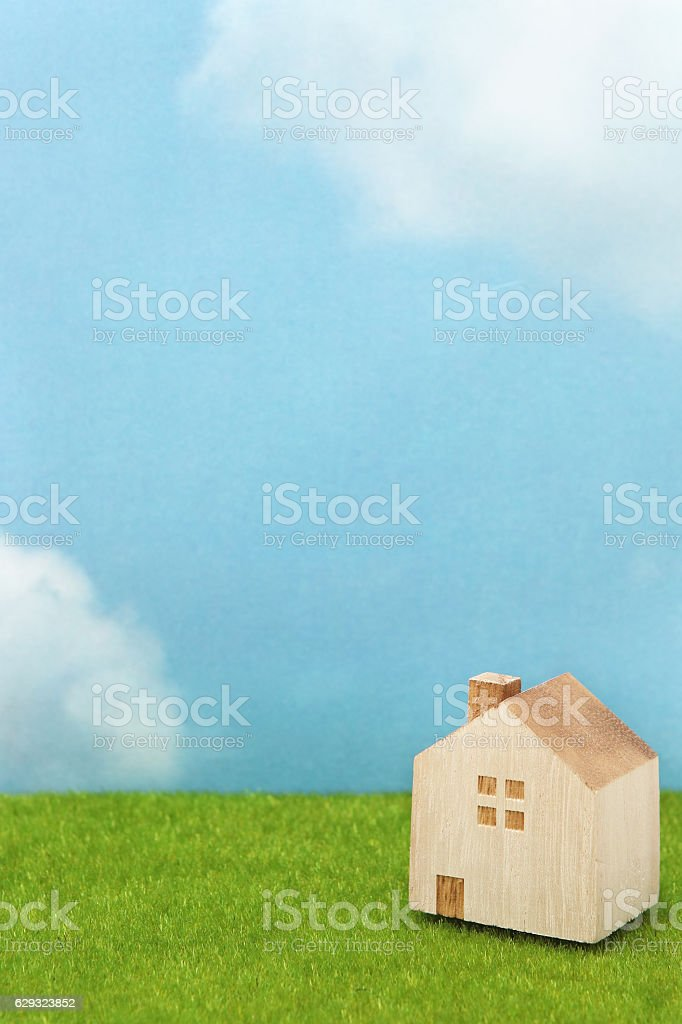 House on green grass over blue sky and clouds. stock photo