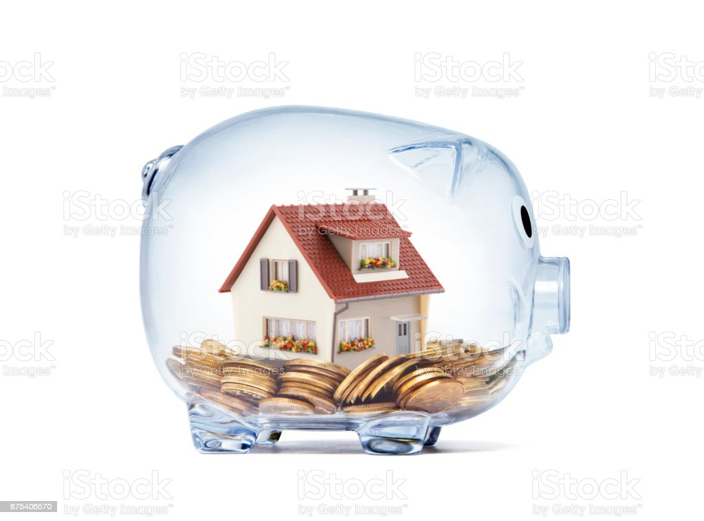 House on money inside transparent piggy bank with clipping path stock photo