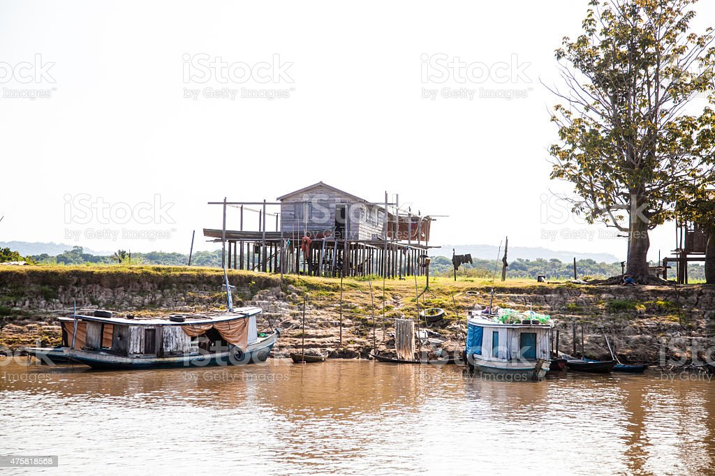 House on Stilts with Boats on the Amazon River stock photo