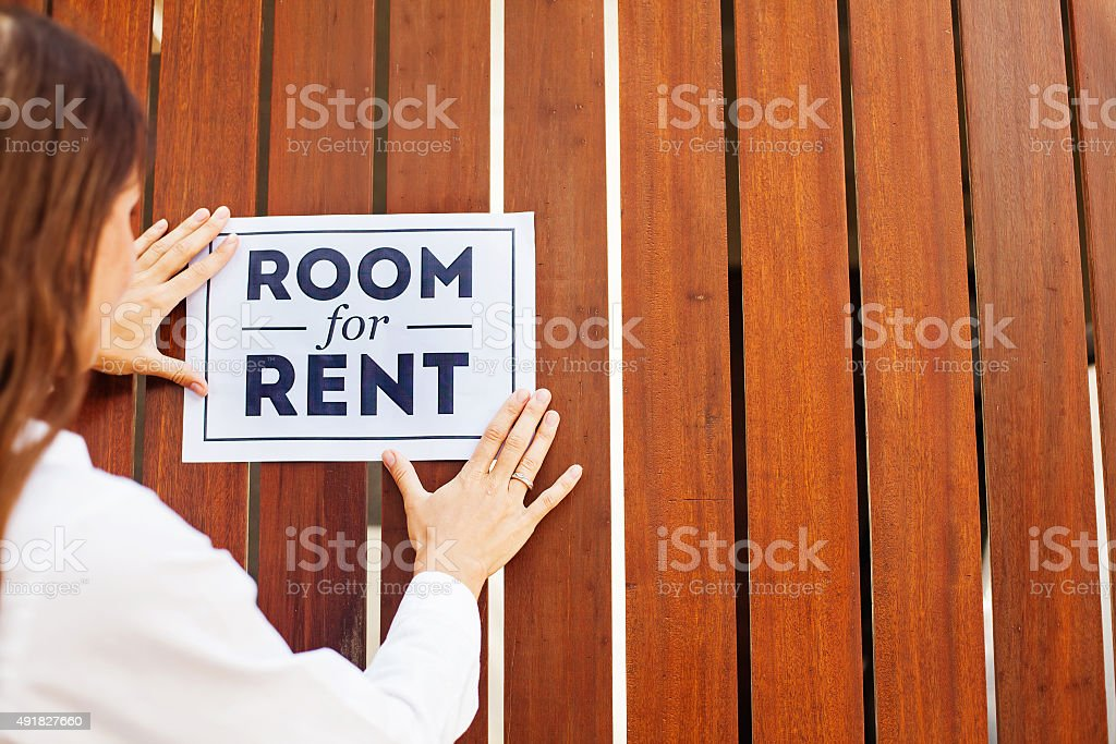 house owner attaching 'Room for rent' sign on a wall stock photo