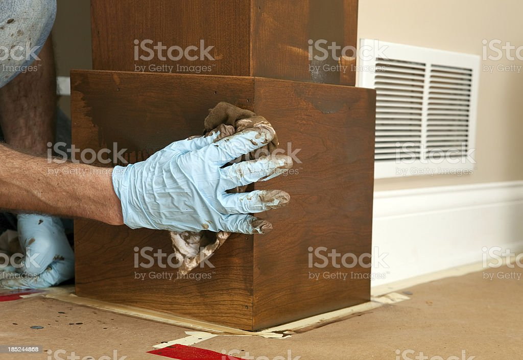 House Painter Applying Stain to a Cherry Column stock photo