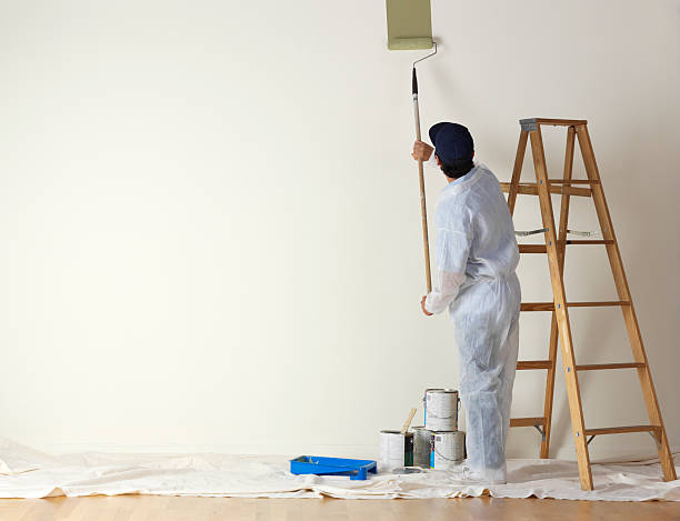 house painter beginning to paint a large wall - painter stock photos and pictures