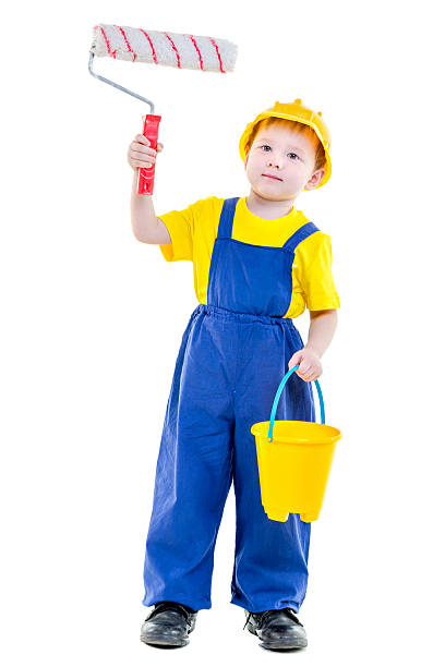 House Painter Kid Cute little boy in blue overalls and hardhat is holding roller and a bucket of paint in hands. Boy is standing isolated on white bib overalls boy stock pictures, royalty-free photos & images