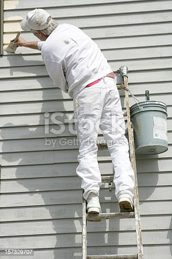 istock House painter leaning towards left to apply paint 157329707