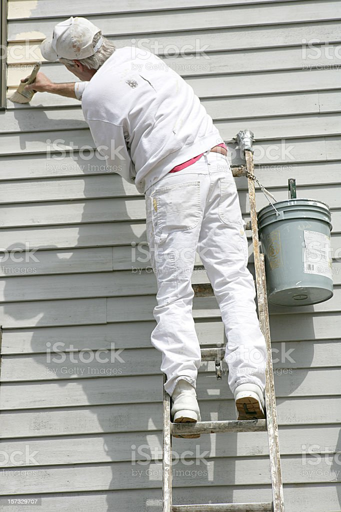 House painter leaning towards left to apply paint stock photo
