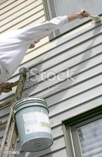 istock House painter on ladder, leaning to reach a corner 172726905