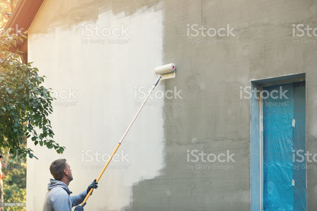 house painter painting building exterior with roller stock photo