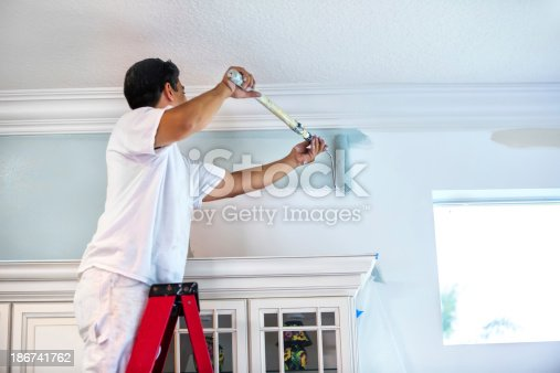A housepainter stands on a ladder to paint the walls inside a residential home.  rr