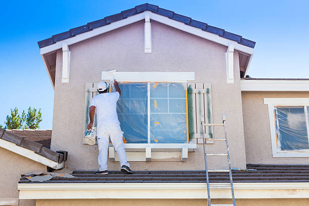 House Painter Painting the Trim And Shutters of Home stock photo