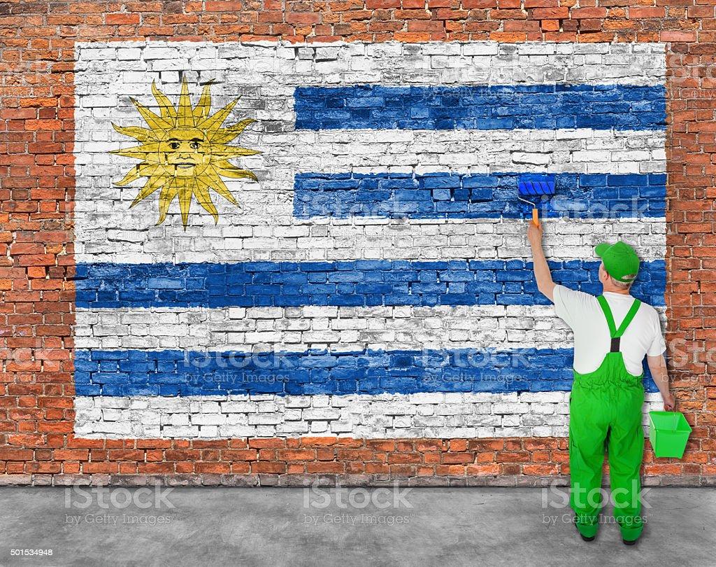 House painter paints flag of Uruguay stock photo