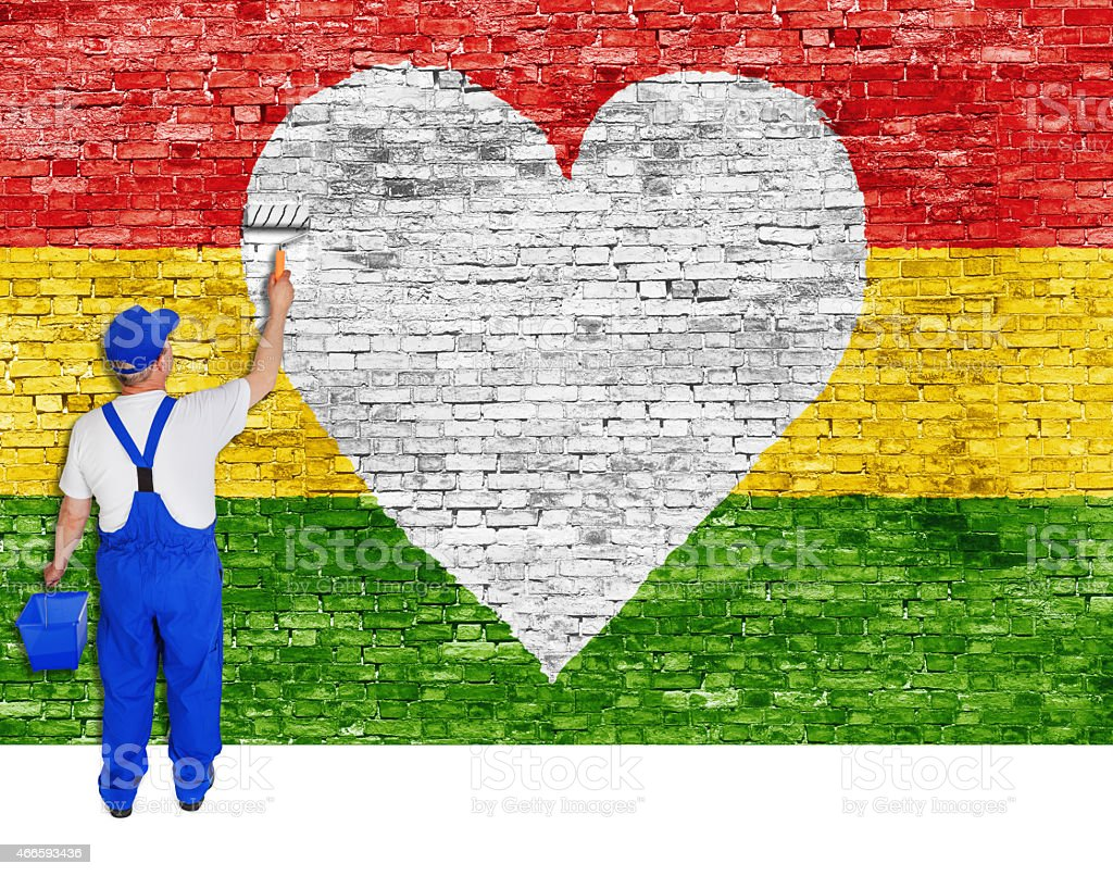 House painter paints heart symbol and flag of Reggae stock photo