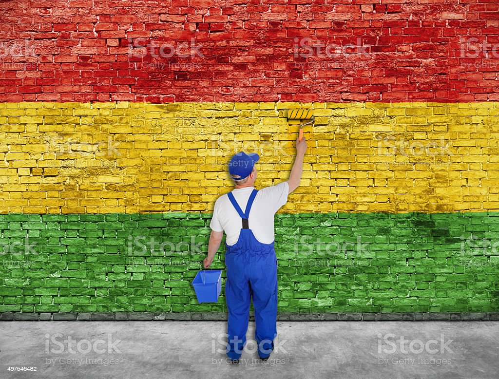 House painter paints Reggae flag on brick wall stock photo