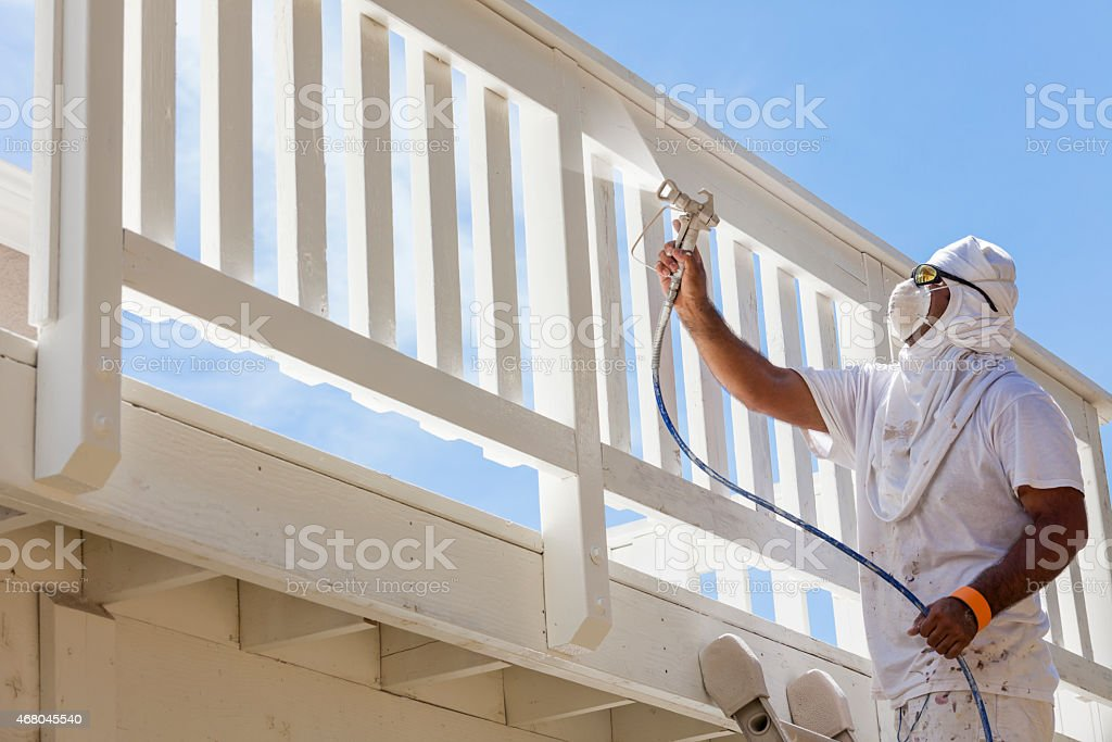 House Painter Spray Painting A Deck of A Home stock photo