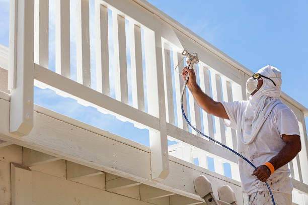 house painter spray painting a deck of a home - painter stock photos and pictures