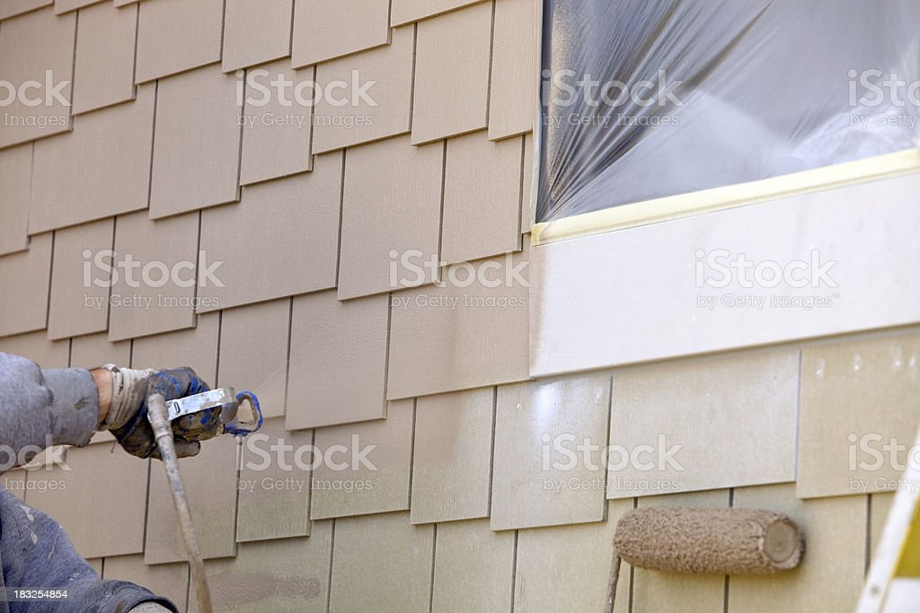 House Painter Spraying Paint on New Siding stock photo