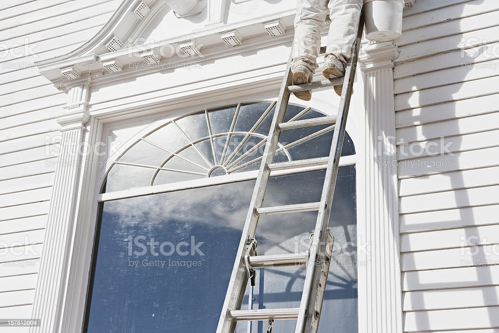 House painter standing on a ladder leaning on a house royalty-free stock photo