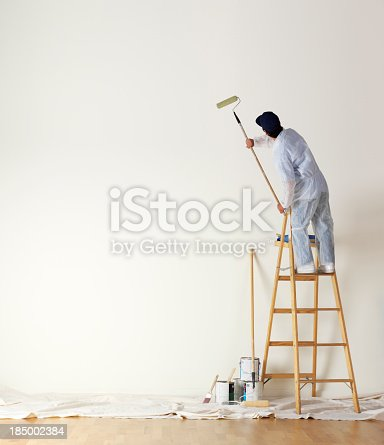 A man dressed in coveralls and standing on a ladder uses a paint roller on a long stick  to paint a large wall.  Several paint cans sit on the painter's cloth draped over a hardwood surface. A large expanse of empty wall is available for copy.