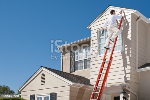 House painter with paint brush painting the trim of a 2nd story window of a Cape Cod Style house.