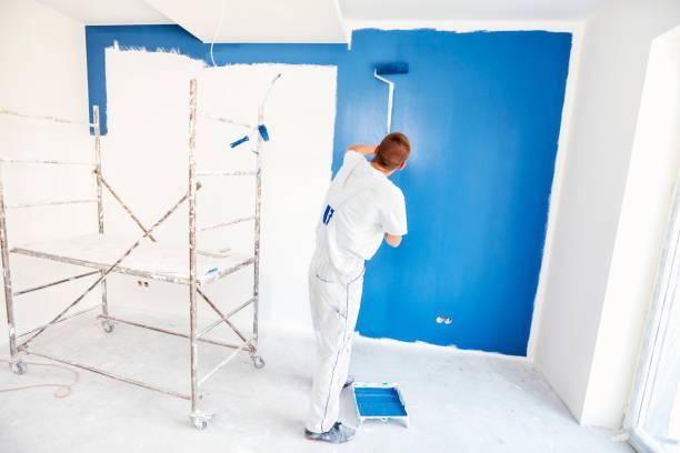 pintores de casa comienza a pintar una pared azul grande - pintor fotografías e imágenes de stock