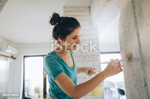 Young woman painting her living room