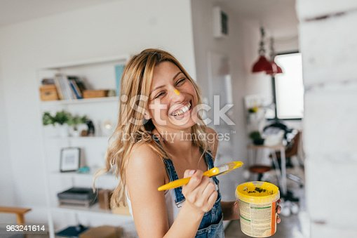 Portrait of a young smiling woman painting her house all by herself