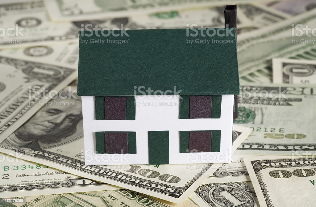 House Payments A minature house on top of a pile of US money. Business Stock Photo