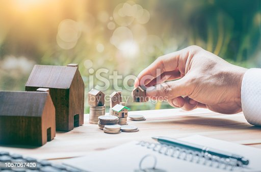 istock House placed on coins Men's hand is planning savings money of coins to buy a home concept concept for property ladder, mortgage and real estate investment. for saving or investment for a house, 1057067420