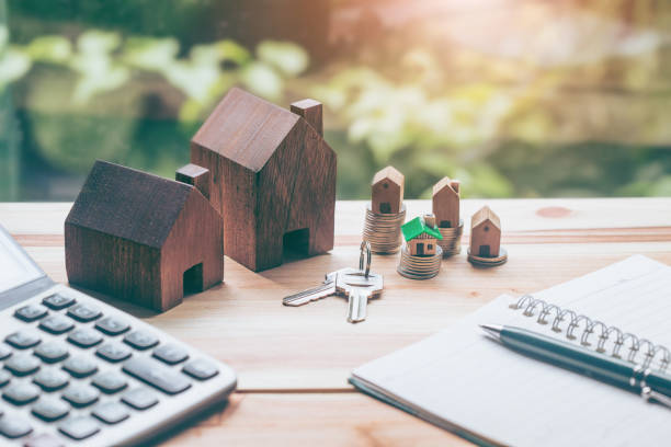 House placed on coins Men's hand is planning savings money of coins to buy a home concept concept for property ladder, mortgage and real estate investment. for saving or investment for a house, stock photo
