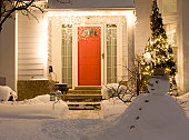 A resident house porch decorated with holiday lights at winter night. A snowman standing in front of the house.
