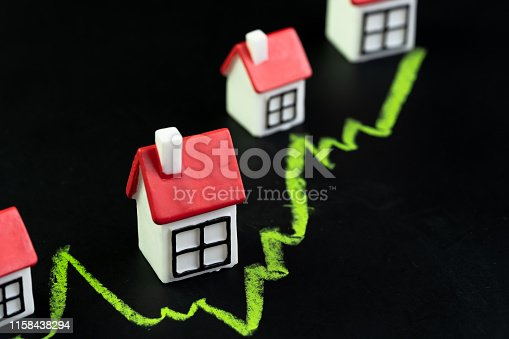 915688450 istock photo House, property or real estate market price go up or rising concept, small miniature house with green line graph going up on black chalkboard 1158438294