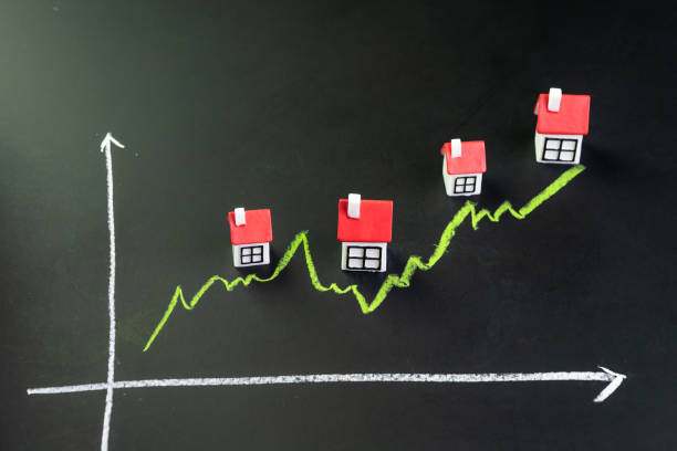 house, property or real estate market price go up or rising concept, small miniature house with green line graph going up on black chalkboard - white background стоковые фото и изображения