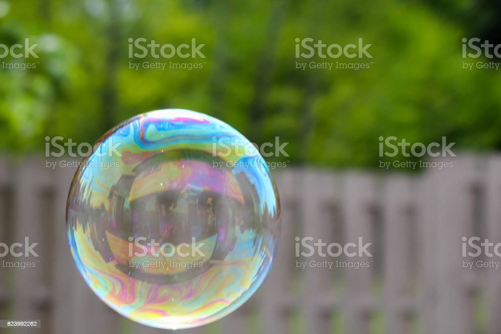 house reflected in a bubble on the left  floating past a out of focus fence. stock photo