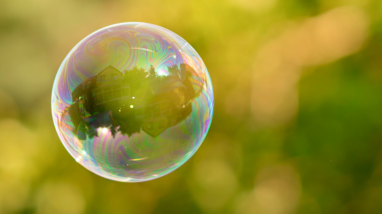 istock House reflection in soap bubble on green, blurred background. 1210086493