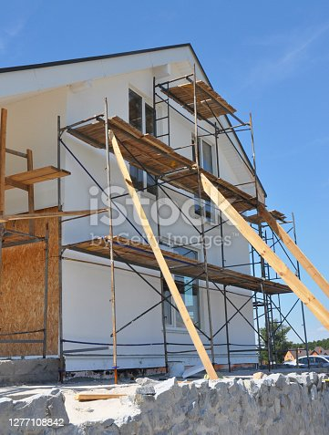 istock House renovation facade with wall insulation, plastering, painting walls. House remodel construction facade with scaffolding outdoors. 1277108842