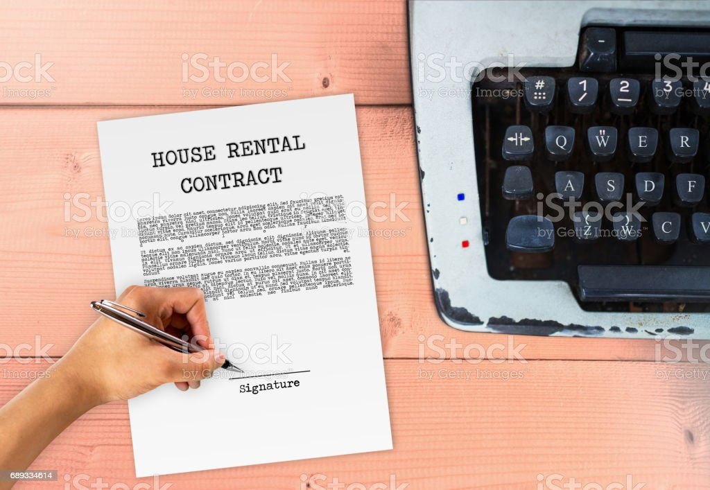 House rental agreement with hand signing on signature paper, with typewriter on wood table, vintage contract sign stock photo
