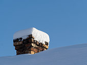 Chimney on the roof of country house covered with deep snow after strong snowfall. Sunny and frosty weather