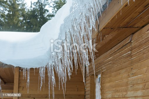 roof of the house with snow and icicles hanging