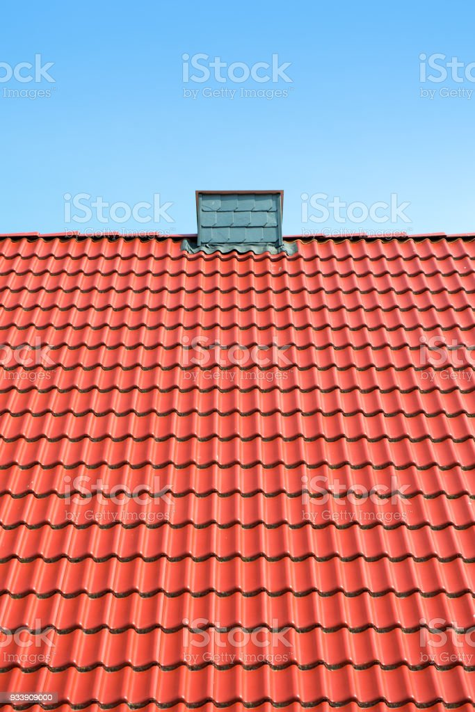 House roof with red bricks and a chimney in front of blue sky stock photo